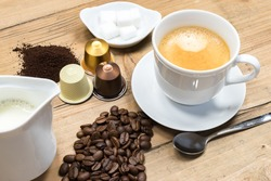 Cup of creamy coffee with fresh roasted and grinded coffee beans, jug of milk, machine capsules and lumps of sugar.
