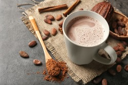 Cup of delicious hot cocoa on grey background