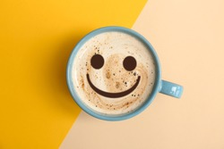 Cup of delicious hot coffee with foam and smile on color background, top view. Happy morning, good mood, inspiration