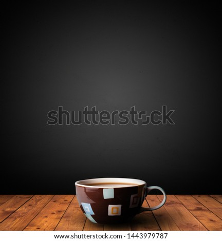 Cup of drink on wooden table with dark background