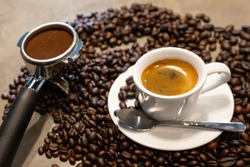 Cup of espresso coffee and portafilter on coffee beans background ,fresh espresso with crema (perfect shot) in the morning at cafe shop