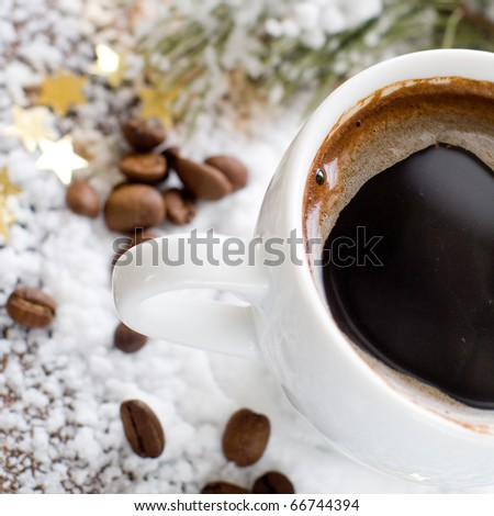Cup of espresso coffee in snow with beans - stock photo