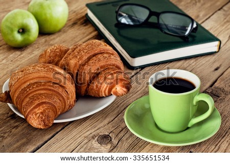 cup of espresso coffee with croissants and notepad on the wooden table. Top view #335651534