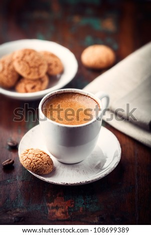 Cup of espresso crema and biscotti on dark wooden table