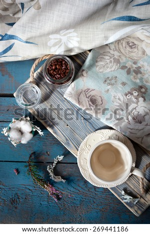 Cup of espresso set on a wooden table with coffee beans, a cup and table linens, natural light setting.