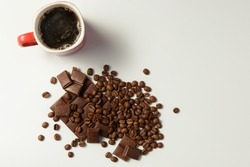 cup of fragrant coffee, beans coffee and chocolate on white background. Top view.