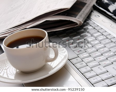 Cup of fragrant coffee on a morning paper