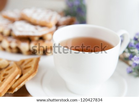 Cup of fragrant tea white porcelain and cookies