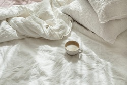 Cup of fresh coffee in bed, morning mood. Linen cotton textile bedclothes. Organic and natural linen. Cozy bedroom interior. Beautiful light.