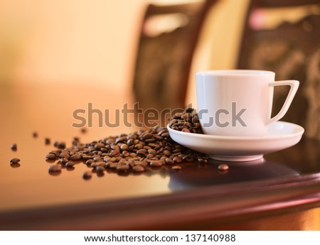 Cup of fresh coffee with the roasted beans on the table as a home interior background