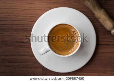 cup of fresh espresso with cleaning blush of coffee machine on table, view from above
