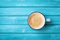 Cup of fresh morning coffee on turquoise wooden table top view
