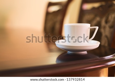 Cup of fresh morning coffee over table with the chairs as a home interior background