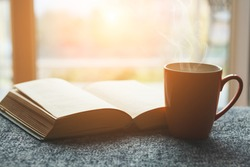 cup of fresh tea or morning coffee and open book at home at morning light, reading book and drinking coffee concept