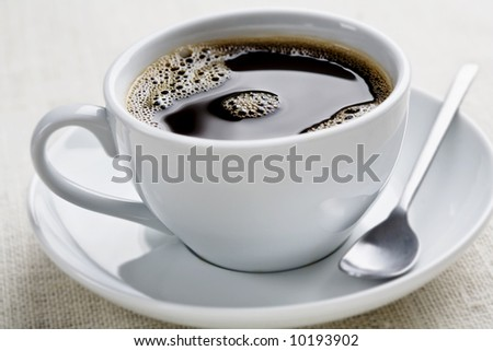 cup of freshly brewed black coffee, focus is on the middle bubbles
