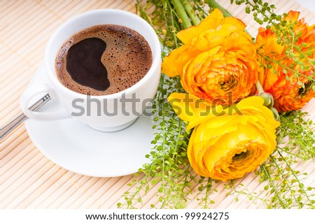 cup of freshly brewed coffee and flowers on the table