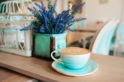 Cup of freshly brewed coffee with milk foam and a pattern in a turquoise-blue porcelain mug on a saucer against a background of violet flowers in a vase. Grab a coffee in the light interior of cafe.