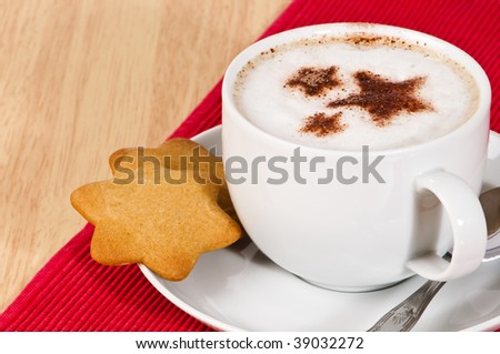 Cup of frothy cappuccino with star shaped biscuits