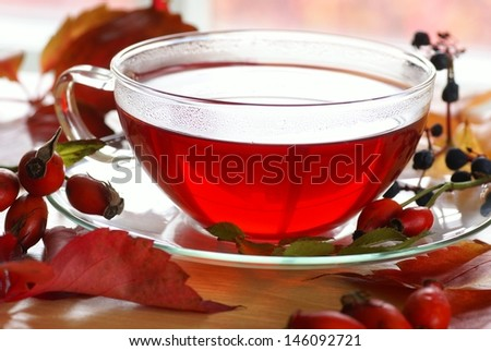 Cup of fruit rosehip tea and autumn leaves and fruits on a table