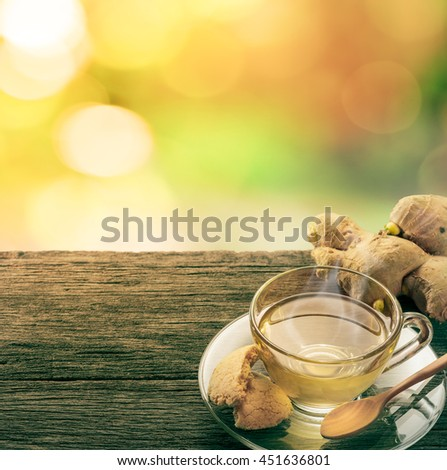 Cup of ginger tea with smoke and cookie on grunge wooden table in garden. #451636801