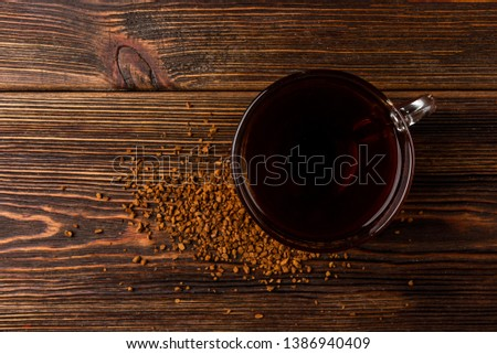 Cup of granulated coffee on dark wooden background.