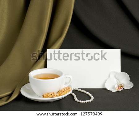 Cup of green tea and cookies with sesame seeds, orchid, pearl necklace and postcard with place for your text