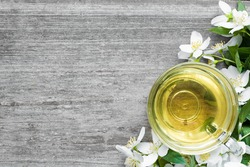 Cup of green tea with jasmine over rustic wooden background. herbal tea Top view with copy space