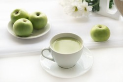 cup of green tea with milk, near apples and a bouquet of chrysanthemums on a white table. good morning