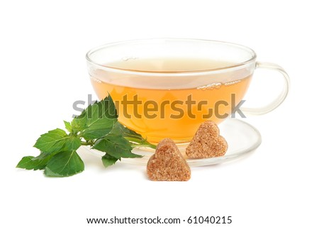 Cup of green tea with mint leaves, lemon and heart-shaped cane sugar on white background