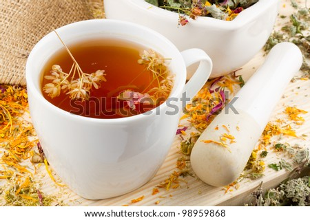 cup of healthy tea, mortar and pestle with healing herbs on wooden table, herbal medicine