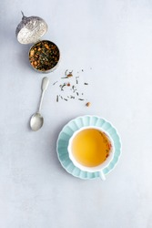 Cup of herbal green tea and dried green tea leaves on light grey background. Tea composition concept. Top view. free space for text.