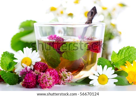 cup of herbal tea and fresh flowers on a white background