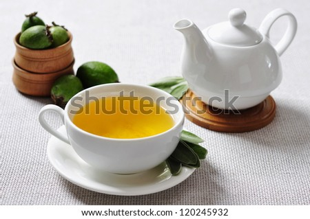 Cup of herbal tea and fresh ripe pineapple guava fruit in wooden bowls