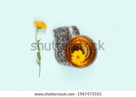 Cup of herbal tea on stone and calendula flower on blue background. Calming drink concept. Foto stock ©