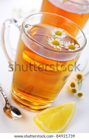cup of herbal tea with chamomile flowers and lemon -healthy lifestyle - stock photo