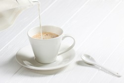 cup of hot cappuccino coffee on a white wood table. Milk being poured into a cup of coffee. Adding milk. horizontal photo