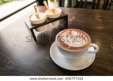 Cup of hot chocolate art  on wooden table in Coffee cafe