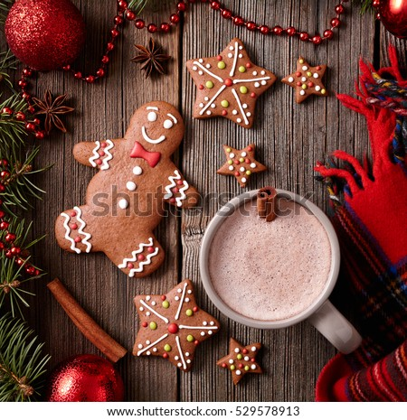 Cup of hot chocolate or cocoa with gingerbread man, warm scarf composition in fir tree decorations frame on vintage wooden table background. Square view