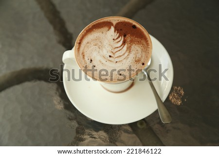 cup of hot chocolate with art creamy milk in cafe