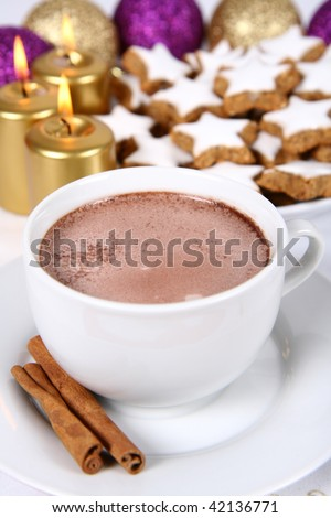 Cup of hot chocolate with cinnamon, star shaped christmas cookies with icing ana gold candles with christmas balls in the background