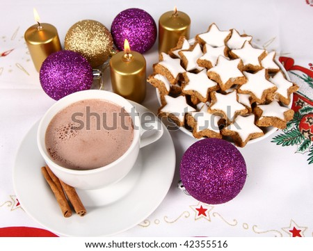 Cup of hot chocolate with cinnamon, star shaped christmas cookies with icing and gold candles with christmas balls on christmas tablecloth