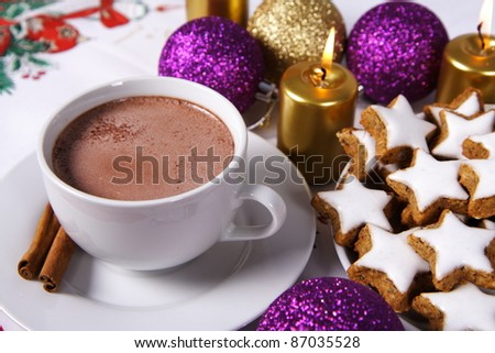 Cup of hot chocolate with cinnamon sticks, star shaped christmas cookies with icing, gold candles and christmas balls