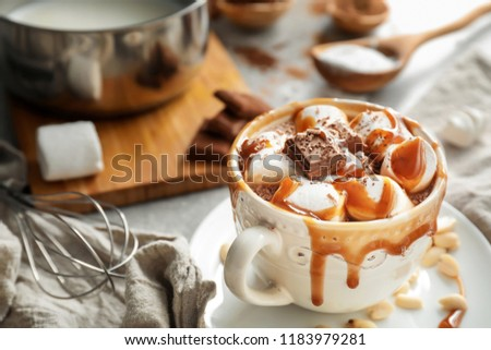 Cup of hot chocolate with marshmallows and caramel on table
