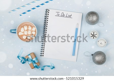 Cup of hot cocoa, gift, holiday decorations and notebook with to do list on blue vintage table from above, christmas planning and mockup. Flat lay style.