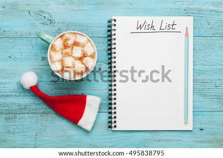 Cup of hot cocoa or chocolate with marshmallow, Santa Claus hat and notebook with wish list on turquoise vintage table from above, christmas planning concept. Flat lay. style.