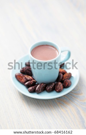 cup of hot cocoa with cocoa beans - food and drink