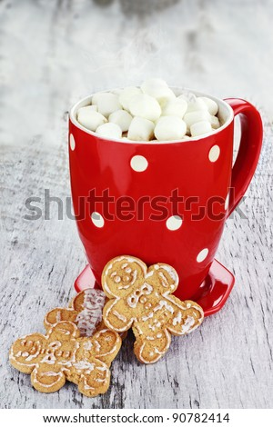 Cup of hot cocoa with marshmallows and cookies on a rustic background.