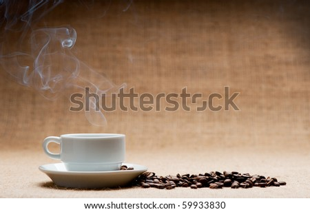 Cup of hot coffee about the ferry and grains of coffee on grunge a background. Old tone