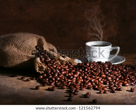 Cup of hot coffee and beans on a dark background