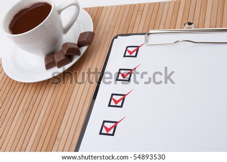 Cup of hot coffee and checklist on clipboard
